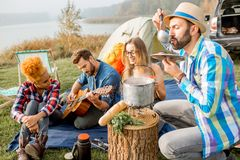 Friends during the outdoor recreation. Multi ethnic group of friends dressed casually having a picnic, cooking soup with cauldron during the outdoor recreation Stock Photo