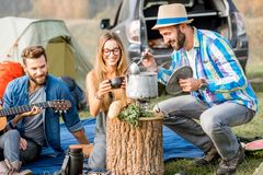 Friends during the outdoor recreation. Multi ethnic group of friends dressed casually having a picnic, cooking soup with cauldron during the outdoor recreation Stock Photography