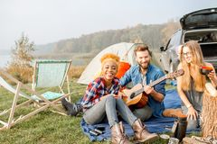 Friends during the outdoor recreation. Multi ethnic group of friends dressed casually having a picnic, cooking soup with cauldron, playing guitar during the Royalty Free Stock Photos