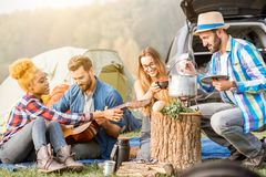Friends during the outdoor recreation. Multi ethnic group of friends dressed casually having a picnic, cooking soup with cauldron, playing guitar during the Stock Image