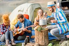 Friends during the outdoor recreation. Multi ethnic group of friends dressed casually having a picnic, cooking soup with cauldron, playing guitar during the Stock Images