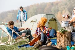 Friends during the outdoor recreation. Multi ethnic group of friends dressed casually having a picnic during the outdoor recreation near the lake Stock Images