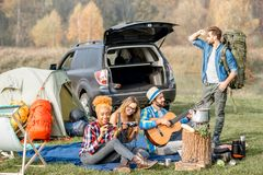 Friends during the outdoor recreation. Multi ethnic group of friends dressed casually having a picnic during the outdoor recreation with tent, car and hiking Royalty Free Stock Photo