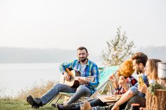Friends during the outdoor recreation. Multi ethnic group of friends dressed casually having a picnic, playing guitar and eating pizza, during the outdoor Stock Photography