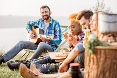 Friends during the outdoor recreation. Multi ethnic group of friends dressed casually having a picnic, playing guitar and eating pizza, during the outdoor Royalty Free Stock Photo