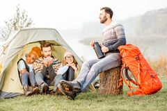 Friends during the outdoor recreation. Multi ethnic group of friends dressed in sweaters warming up together sitting during the outdoor recreation near the tent Royalty Free Stock Photos