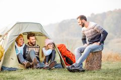 Friends during the outdoor recreation. Multi ethnic group of friends dressed in sweaters warming up together sitting during the outdoor recreation near the tent Royalty Free Stock Image