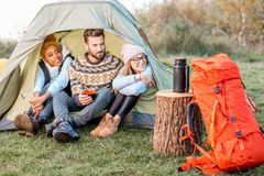 Friends during the outdoor recreation. Multi ethnic group of friends dressed in sweaters warming up together sitting in the tent during the outdoor recreation Royalty Free Stock Image