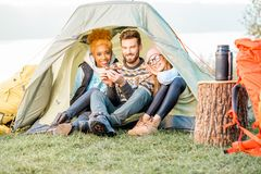 Friends during the outdoor recreation. Multi ethnic group of friends dressed in sweaters warming up together sitting in the tent during the outdoor recreation Stock Image