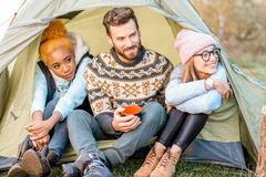Friends during the outdoor recreation. Multi ethnic group of friends dressed in sweaters warming up together sitting in the tent during the outdoor recreation Royalty Free Stock Photography