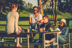 Multi-ethnic group of friends drinking coffee and chatting in a park.  Stock Images