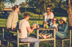 Multi-ethnic group of friends drinking coffee and chatting in a park.  Royalty Free Stock Photos