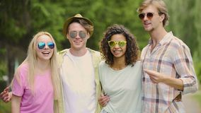 Multi-ethnic group of friends having fun and relaxing in park, vacation, meeting. Stock footage stock video footage