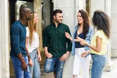 Multi-ethnic group of friends having fun together in urban background. Multi-ethnic group of young people having fun together outdoors in urban background. group royalty free stock photos
