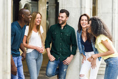Multi-ethnic group of friends having fun together in urban background. Multi-ethnic group of young people having fun together outdoors in urban background. group royalty free stock images