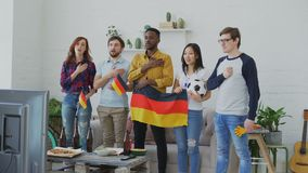 Multi-ethnic group of friends listening and singing German national anthem before watching sports championship on TV. Multi-ethnic group of friends sport fans stock footage