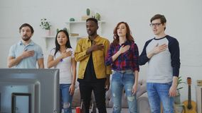 Multi ethnic group of friends sport fans singing national anthem before watching sports championship on TV together at. Home indoors stock video