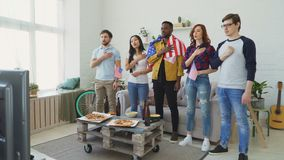 Multi ethnic group of friends sport fans singing national USA anthem before watching sports championship on TV together. At home indoors stock video footage