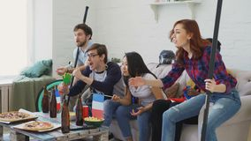Multi ethnic group of friends sports fans with French national flags watching hockey championship on TV together. Cheering up their favourite team at home stock video