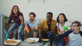 Multi-ethnic group of friends sports fans with German flags watching football championship on TV together at home and. Multi-ethnic group of friends sports fans stock footage
