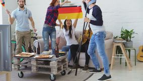 Multi ethnic group of friends sports fans with German national flags watching hockey championship on TV together. Cheering up their favourite team at home stock footage