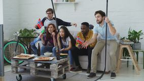 Multi ethnic group of friends sports fans with Norwegian national flags watching hockey championship on TV together. Cheering up their favourite team at home stock footage