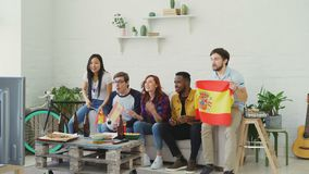 Multi-ethnic group of friends sports fans with Spanish flags watching football championship on TV together at home and. Multi-ethnic group of friends sports fans stock video footage