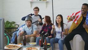 Multi ethnic group of friends sports fans with USA national flags watching winter olympic games on TV together cheering. Up favourite team at home indoors stock footage
