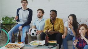 Multi ethnic group of friends sports fans watching football championship on TV together eating pizza and drinking beer. At home indoors stock video footage