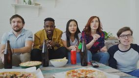 Multi ethnic group of friends sports fans watching sport match on TV together celebrating goal of favourite team while. Eating snacks and drinking beer stock video footage