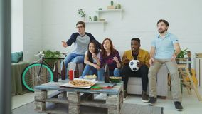 Multi ethnic group of friends sports fans watching sport match on TV together eating snacks and drinking beer at home