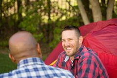 Multi-Ethnic group of friends talking and camping. Royalty Free Stock Photography