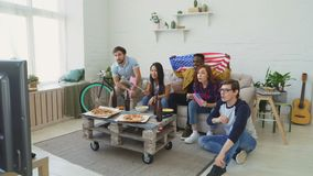 Multi ethnic group of friends with USA national flags watching sport championship on TV together cheering up their. Favourite team at home indoors stock video