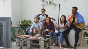 Multi ethnic group of friends with USA national flags watching sport championship on TV together and happy about winning. Favourite team at home indoors stock footage