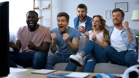 Multi-ethnic group of friends watching football game at home, celebrating goal. Stock photo stock image