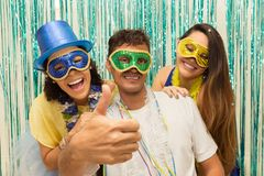 Group of Brazilian friends wearing Carnaval costume. Man makes a. Multi ethnic group of friends is wearing Carnaval masks. Happiness and euphoria. Man points Stock Image