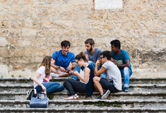 A multi-ethnic group of guys having fun chatting on the stairs o. SAN GIMIGNANO, ITALY - JUNE 11, 2016 - A multi-ethnic group of guys having fun chatting on the stock images