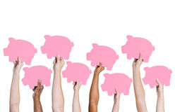 Multi-Ethnic group holding piggybank Stock Photo