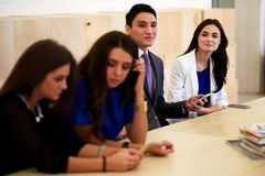 Multi ethnic group of a intelligent international students working on cell telephone during break between lectures Stock Images