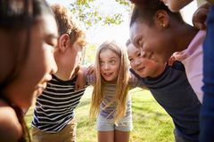 Multi-ethnic group of kids embracing, looking at each other royalty free stock photos