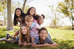 Multi-ethnic group of kids lying on each other in a park stock photography