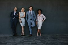 Multi-ethnic group of laughing business people. Full length portrait of multi-ethnic group of business colleagues laughing against a wall. Team of business Royalty Free Stock Images