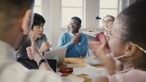 Multi ethnic group at office business meeting. Young diverse partners discuss ideas, then start clapping and smiling 4K.