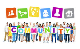 Multi-Ethnic Group Of People Holding Community Placards. Multi-ethnic group of people holding 9 letters of placards forming community Royalty Free Stock Images