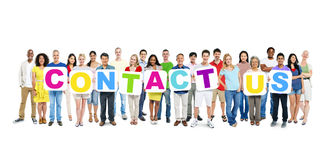 Multi-Ethnic Group Of People Holding Contact Us. Multi-ethnic group of people holding cardboards forming contact us Stock Photography