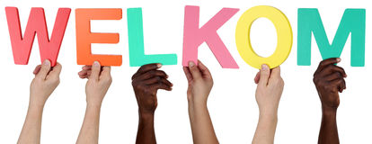 Multi ethnic group of people holding the Dutch word welkom welco Stock Images