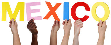 Multi ethnic group of people holding the word Mexico. Isolated Royalty Free Stock Photography