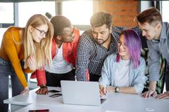Multi-Ethnic Group of People Working Together indoors. Multi-Ethnic Group of People standing near women with violet hair, sharing with her laptop, reading all royalty free stock photography