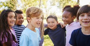 Multi-ethnic group of schoolchildren laughing, outdoors stock photo