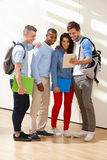 Multi-Ethnic Group Of Students In Classroom With Digital Tablet. Looking into It Royalty Free Stock Image